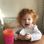 Toddler showing her tongue while eating her morning hipp organic porridge with her juice in her pink non-spill cup