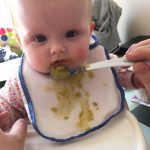 Spoon feeding a baby, the bib is covered in baby food
