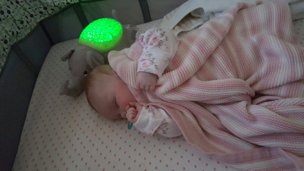Baby wrapped up in her blanket asleep with a dummy and an elephant white noise machine