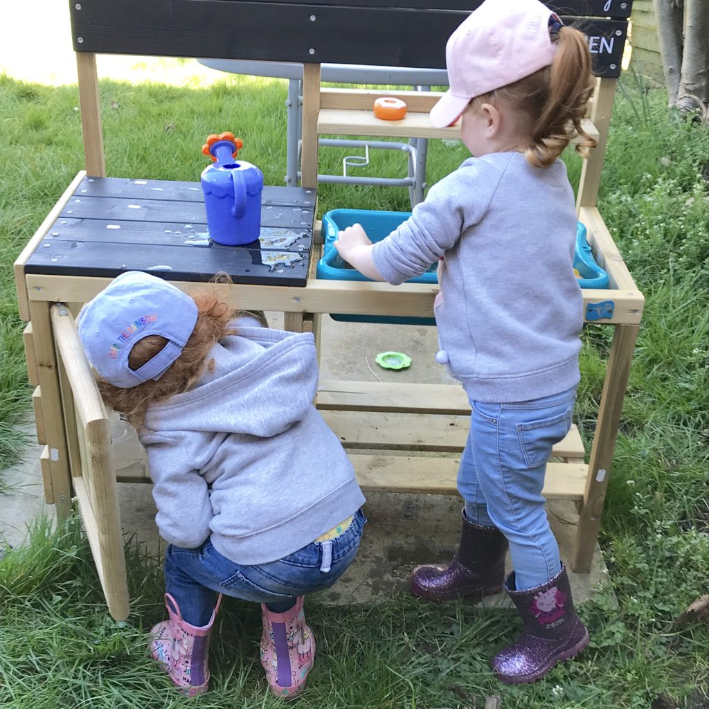 Amelia and Lilly playing in the garden with their mud kitchen. This is on our toddler summer bucket list