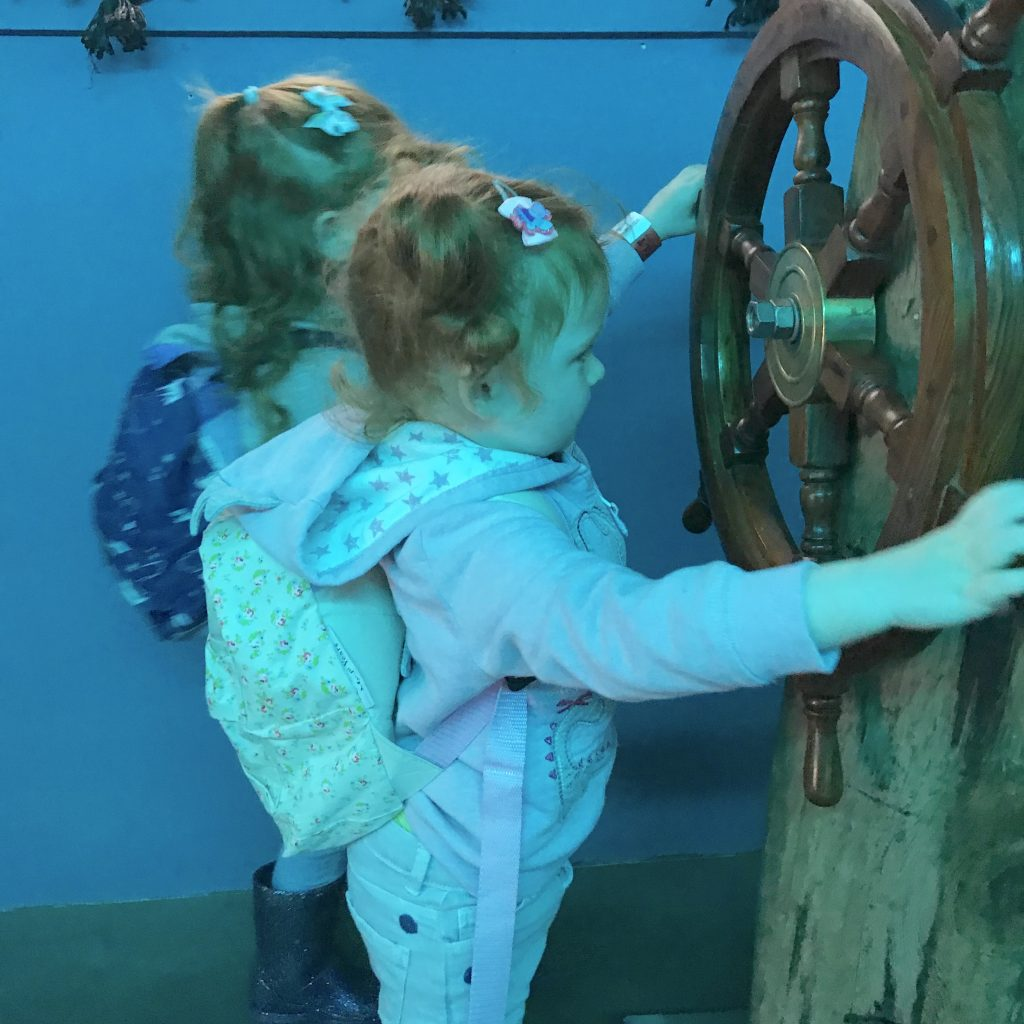 Two girls wearing their backpacks, exploring the underwater area of All Things Wild nature centre in Evesham.
