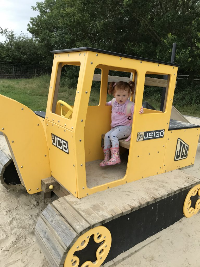 A girl playing on a tractor in the play area at All Things Wild nature centre