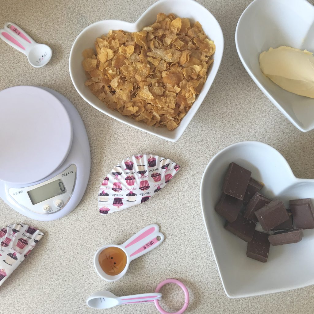 A photo of the ingredients to make cornflake cake. Butter, cornflakes, chocolate and syrup. The photo is decorated with cupcake cases.