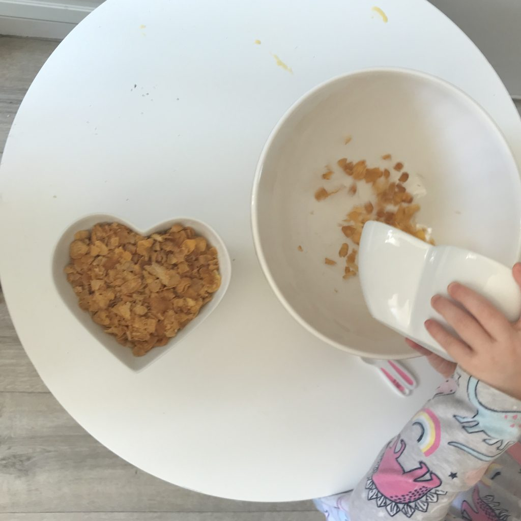 A photo of a Childs hands pouring cornflakes from one bowl to another