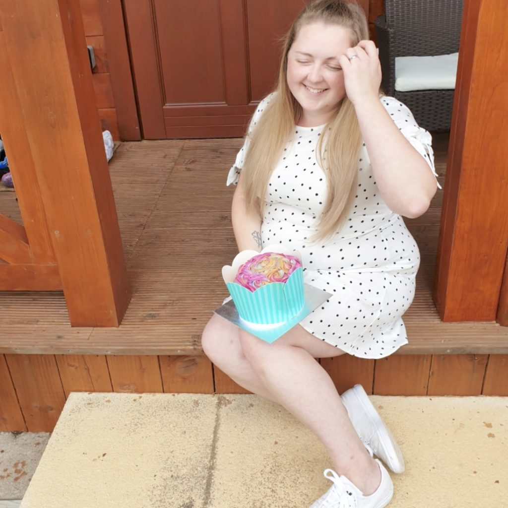 A photo of me with my cupcake birthday cake sitting on the step of the cabin at Northwick Farm Lodges