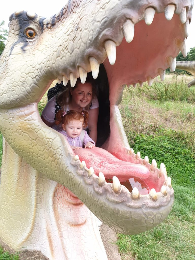 Mum and daughter inside a dinosaur head at All Things Wild nature center in Evesham