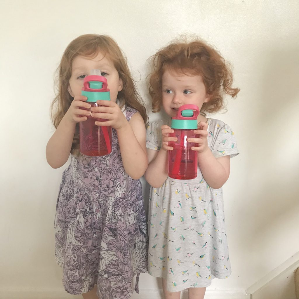 A photo of two girls holding up their new water bottles ready for nursery. This is a great back to nursery/preschool essential
