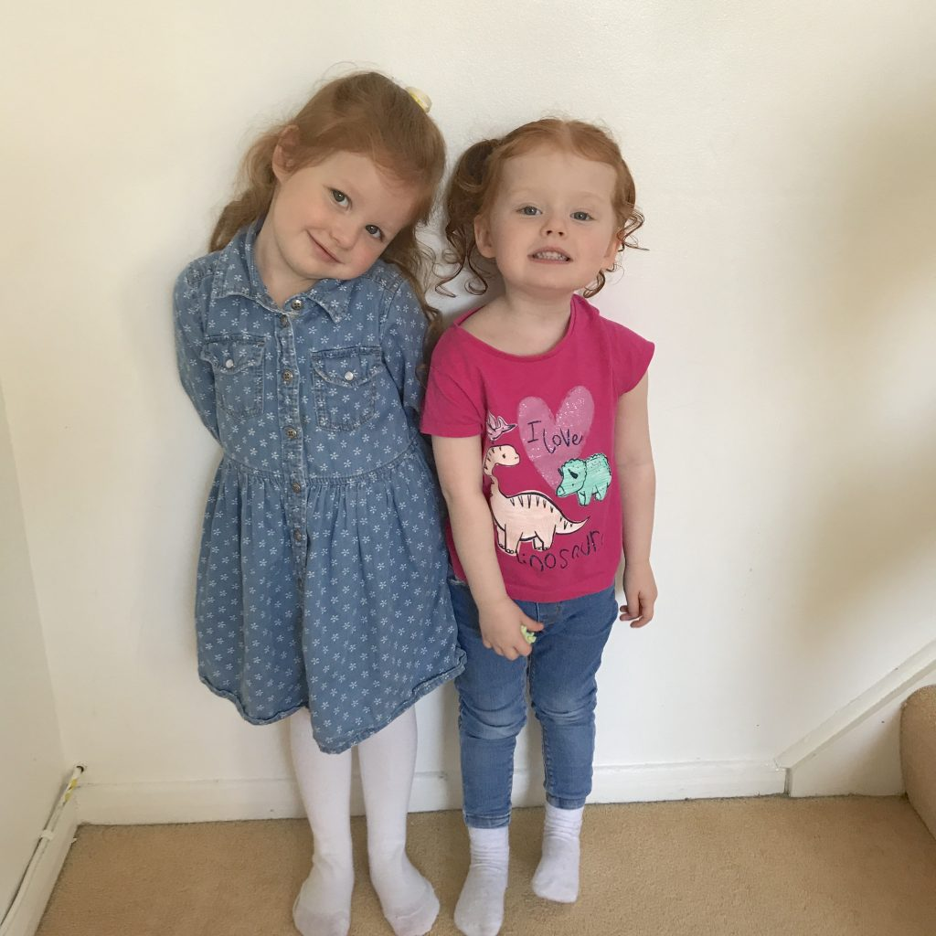 Amelia on her first day back to nursery standing next to her sister lilly