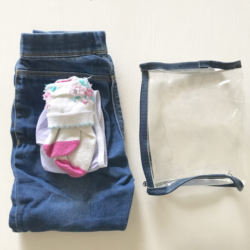A photo of a wetbag with a change of trousers, pants and socks next to it. This is a great back to nursery/preschool essential