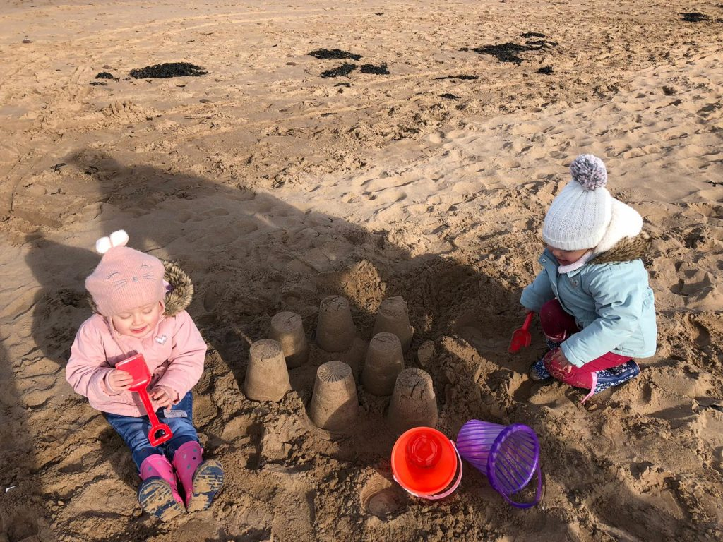 A photo of two girls building sand castles with buckets and spades on the beach at Minehead
