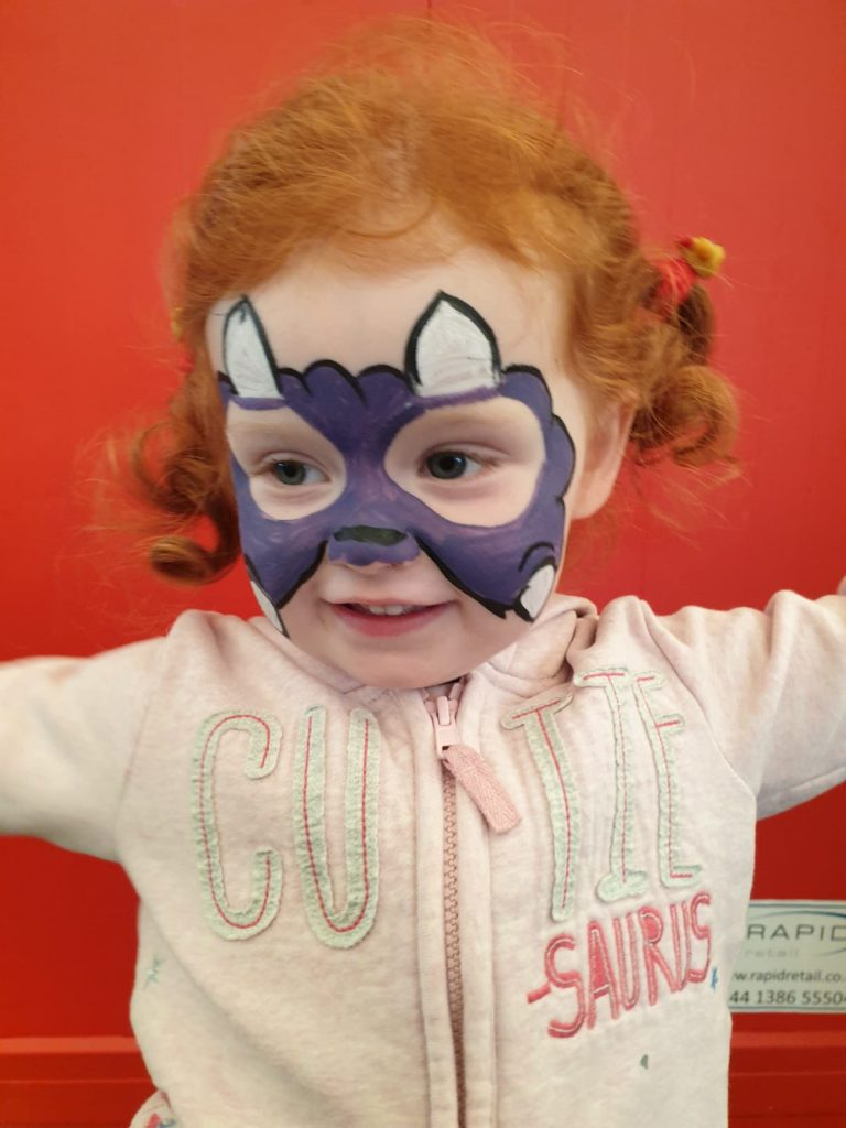 A photo of a girl with their face painted as a purple dinosaur