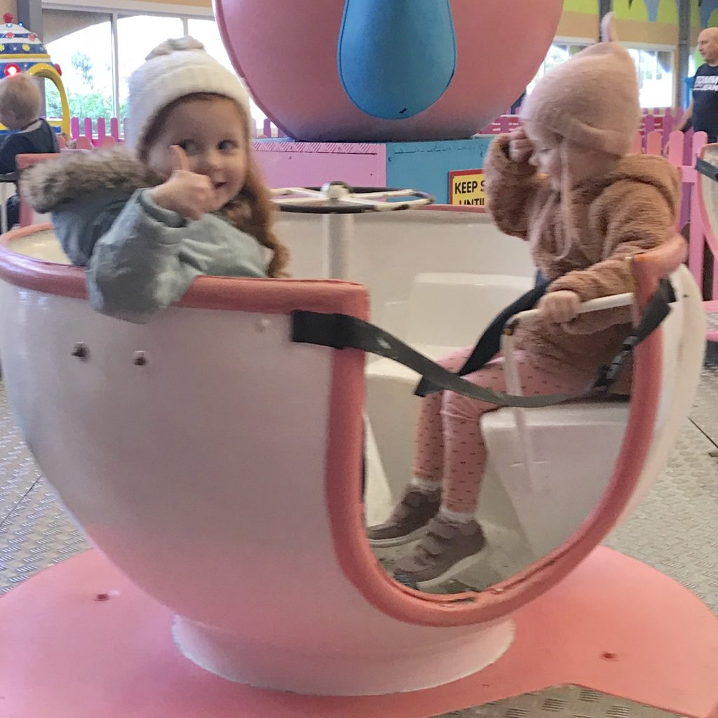 A photo of two girls on a teacups ride in the tots funfair at butlins minehead