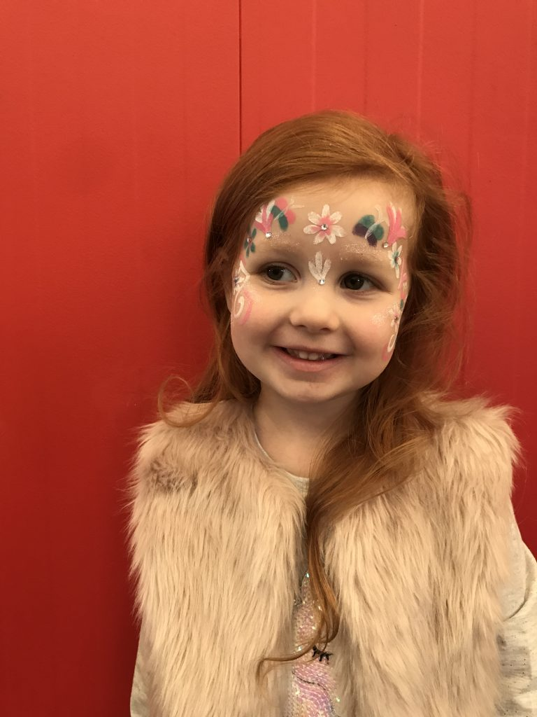 A photo of a girl with their face painted with butterflies and flowers