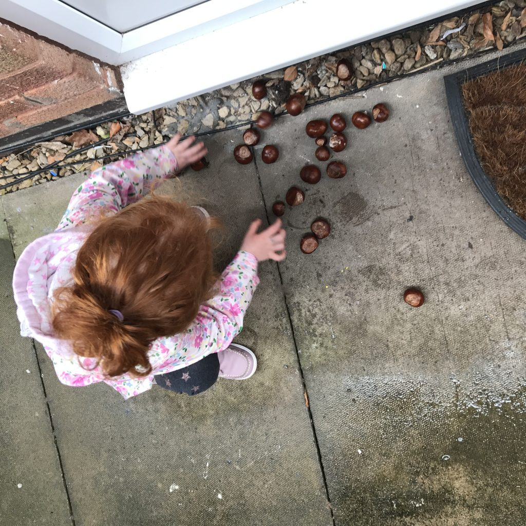 A photo of a girl lining up conkers on a doorstep