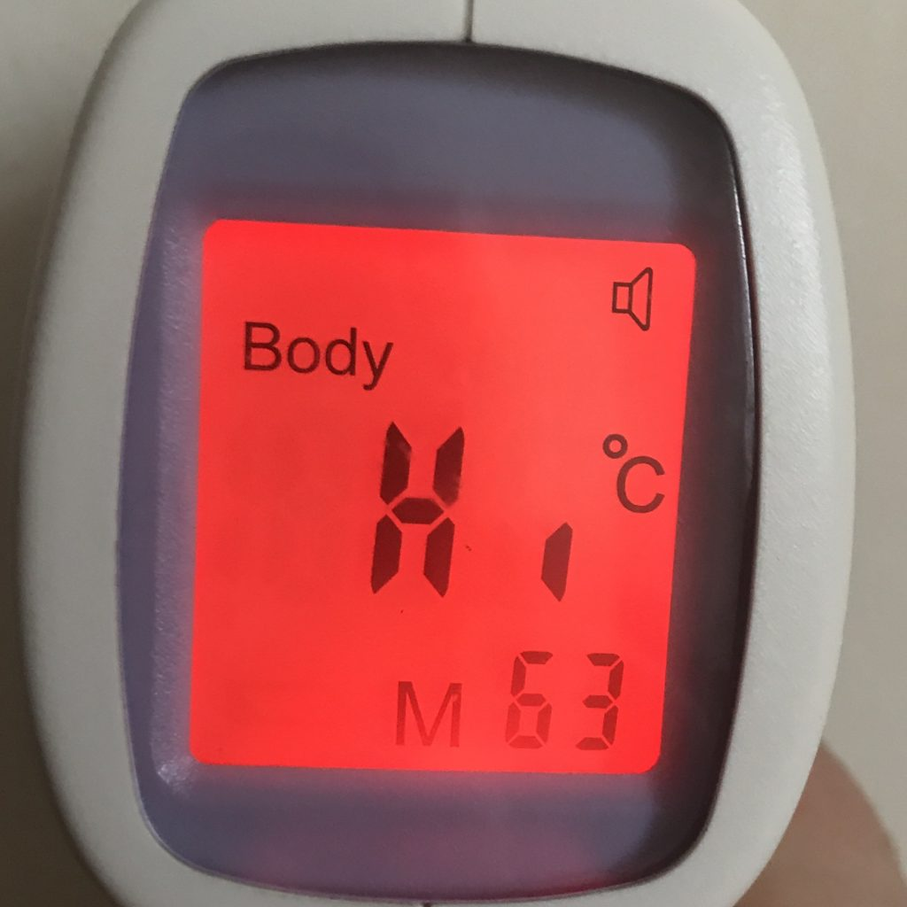"A no touch thermometer displaying ""Hi"""