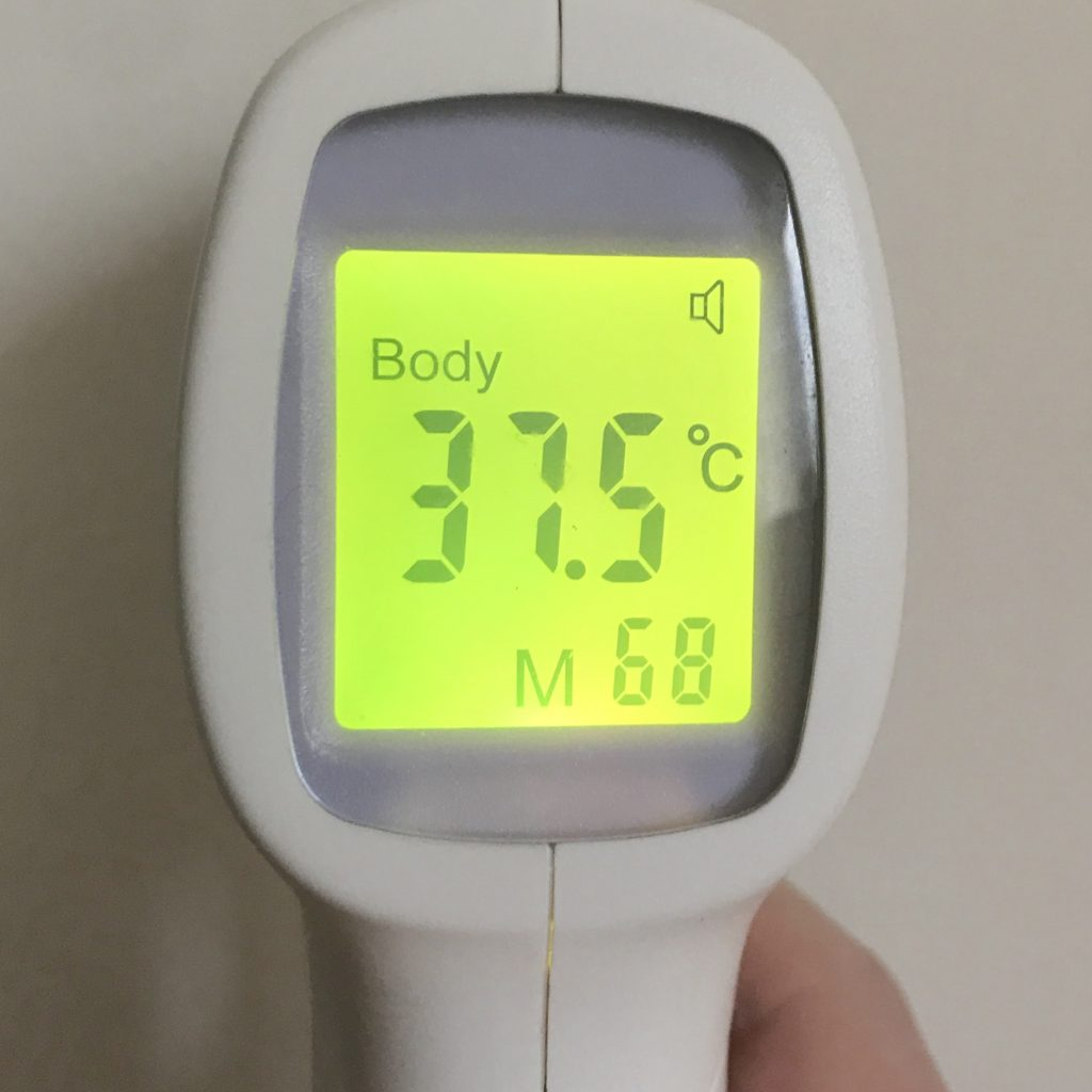 A no touch thermometer displaying 37.5 degrees